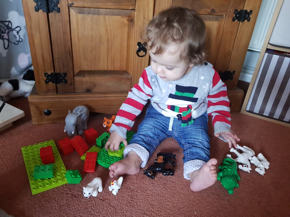 Christmas jumper one year old playing with Duplo