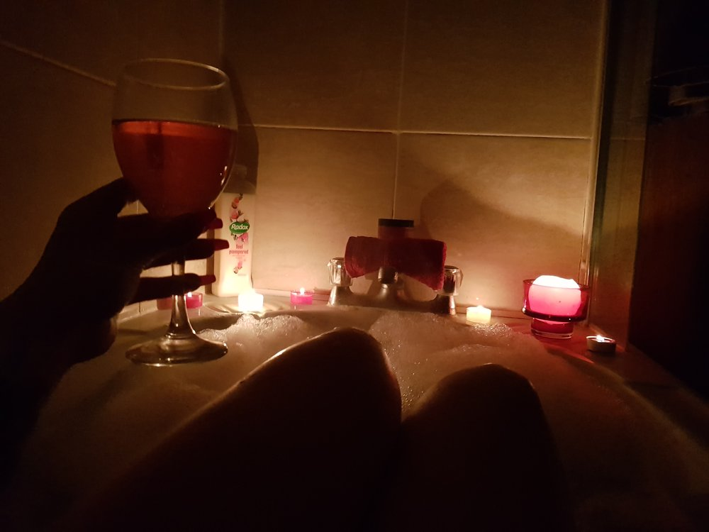 Wine with a candle lit bubble bath