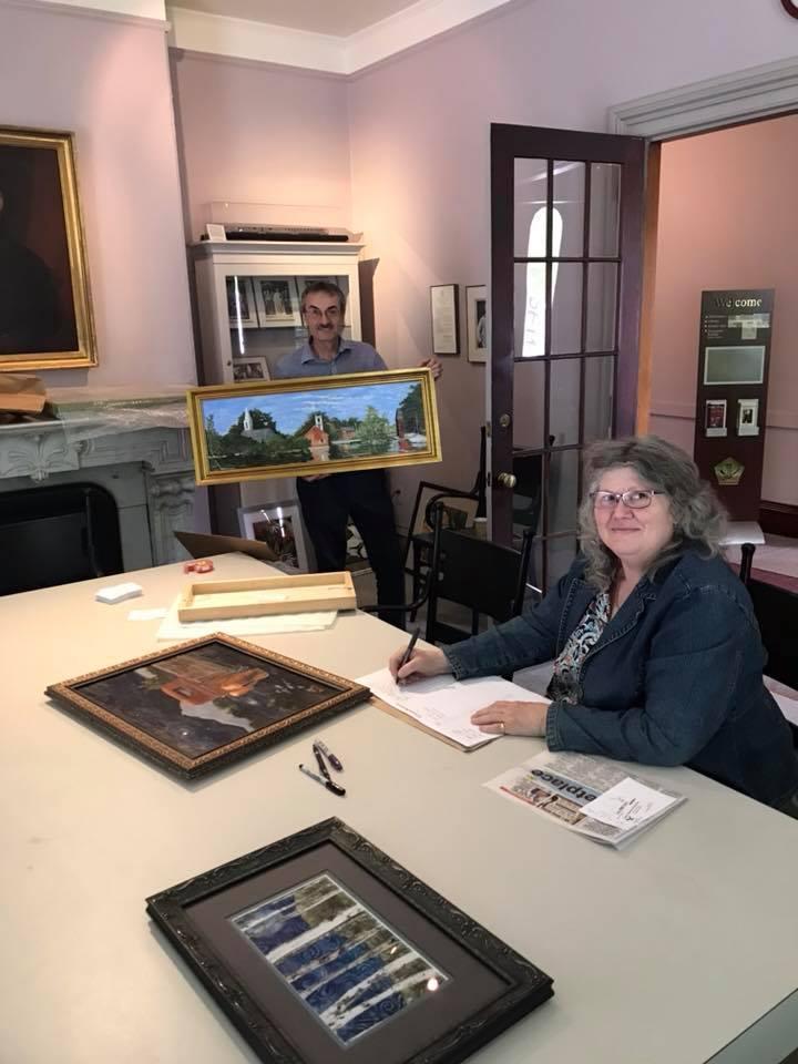 Alicia Drakiotes preps for the All Around Monadnock exhibit with HSCC Executive Director Alan Rumrill.