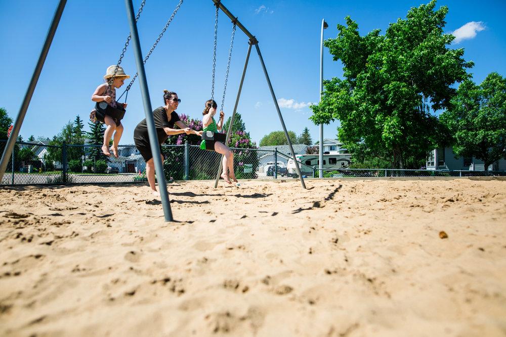 mom pushing kids on the swing