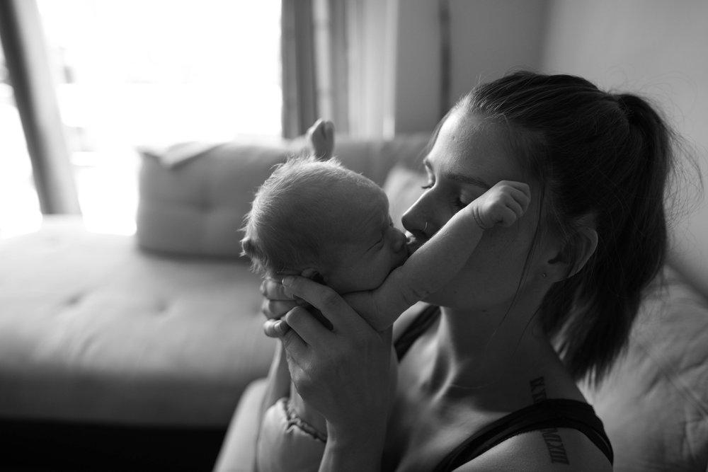Mother kissing newborn son.  Edmonton newborn Photographer lindsay Mills