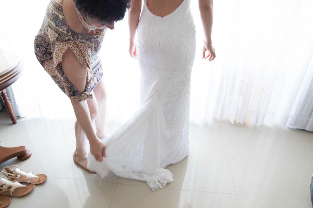 Mother helping bride with dress. destination wedding