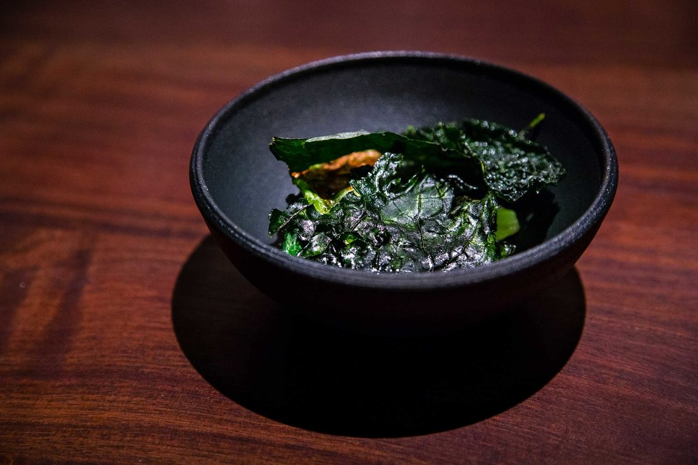 Kale and cabbage chips blistered over the fire or fermented with a broth made from the leaves.