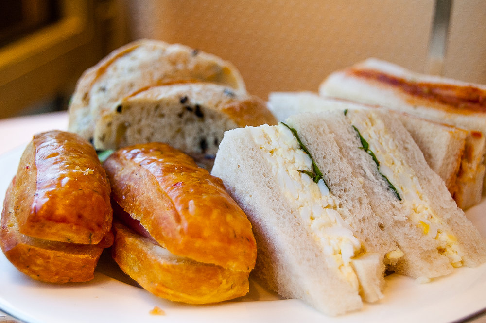 Bottom tier: finger sandwiches. Cucumber with Goat Cheese on Olive Crostini;Egg;Tomato Pesto; and Smoked Salmon