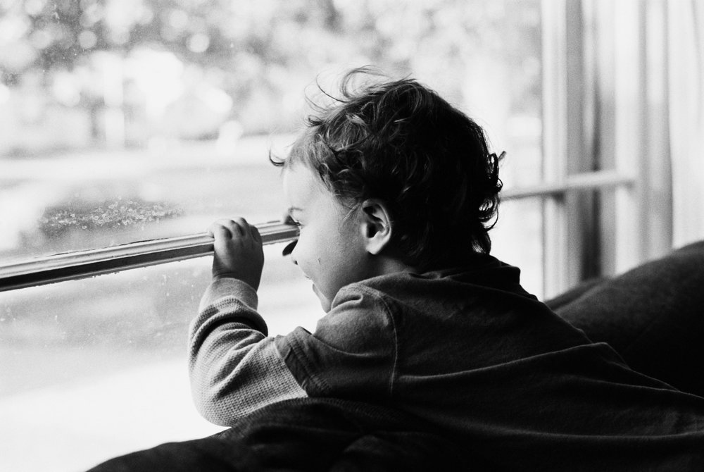 Moody portrait of excited curly haired 3 year old boy waiting for ice cream and looking out the window in eager anticipation. Lifestyle in-home session in Grand Rapids, Michigan. Ashley Burnside Photography.