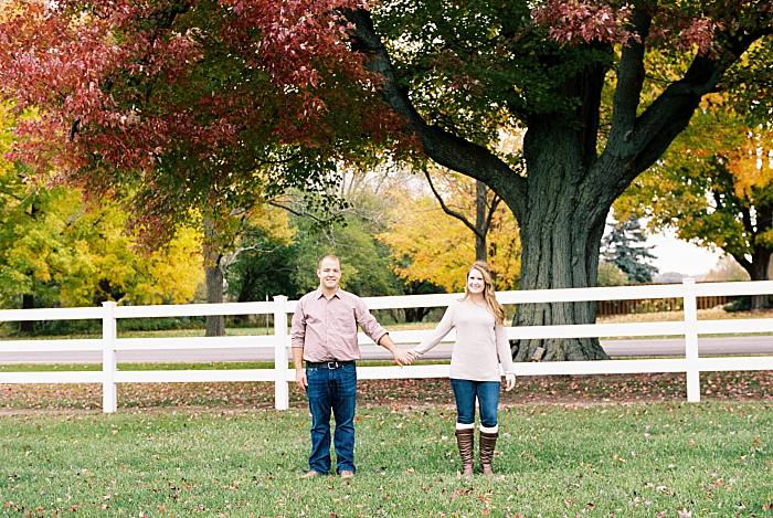 Grand Rapids engaged couple holds hands under colorful changing leaves in front white picket fence in the countryside. Colorful cozy romantic fall engagement session in Michigan. Colors of the leaves are vibrant and look beautifully pastel on film for this soft, romantic engagement session.