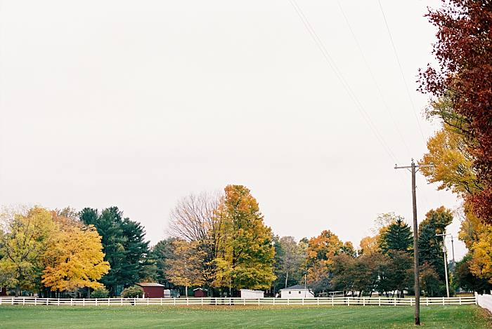 white picket fence and the vibrant colors of fall contrast along the countryside in Kalamazoo/Portage, Michigan