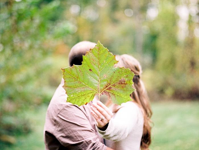 couple poses and kisses behind giant fallen leaf during this colorful pastel fall engagement session in Grand Rapids Michigan