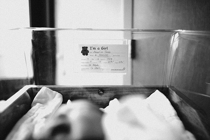 black and white film photo of Newborn baby lays in hospital bassinet during Grand Rapids hospital lifestyle newborn session