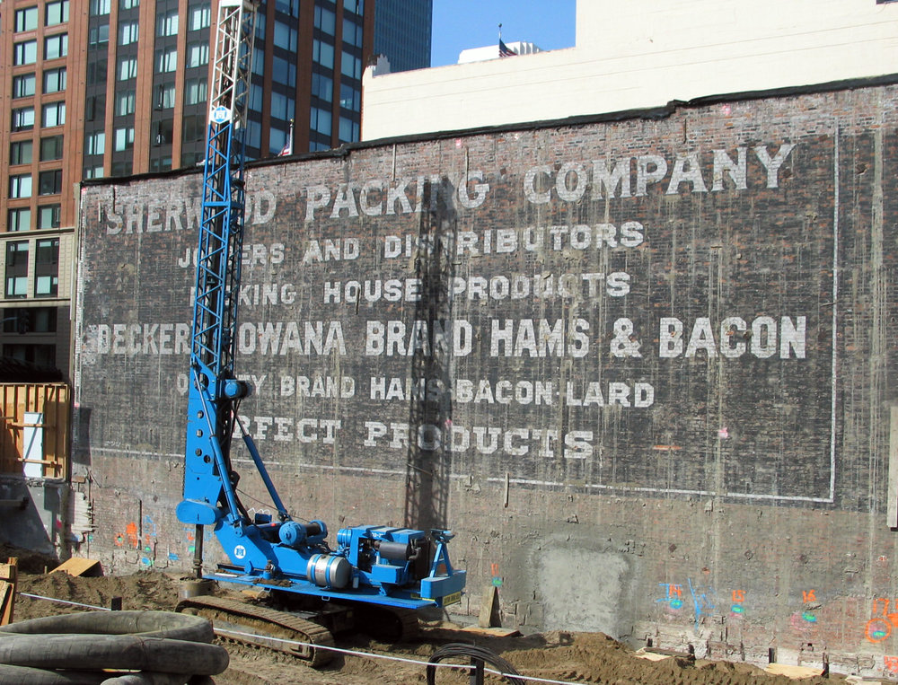 Sherwood Packing Company.  In 2008 a building on the corner of Hawthorne St and Howard St was torn down to make room for a new high-rise. For a period of a few weeks this wonderful wall advertisement for Sherwood Packing Company and their products was exposed before being completely and permanently obscured by the new construction.