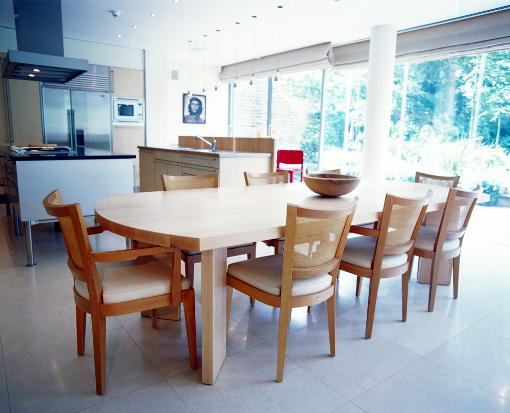 Contemporary, full-size dining table to seat eight  The unique joinery and construction of this solid Canadian maple table ensures that there is no visible attachment between the legs and table base. Sleek, sculptural lines and surfaces are all that are visible on the underside when sitting in the sunken living entertainment room adjacent to the kitchen dining area. Commissioned by  CardenCunietti  for a private residence in Holland Park.