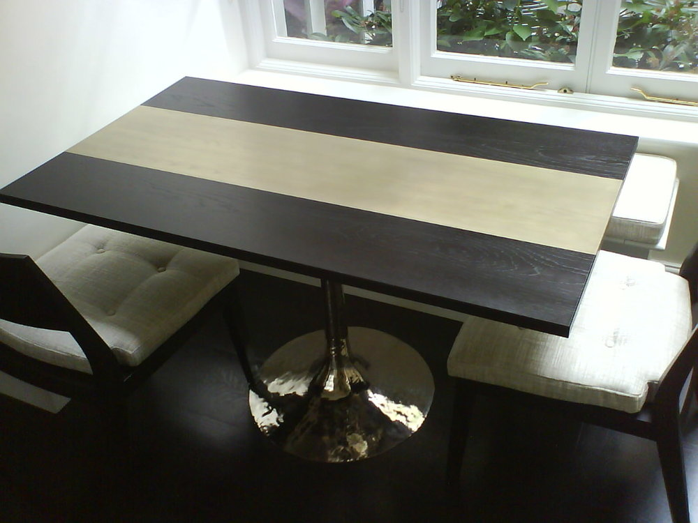 Kitchen eating area table  The gold hammered pedestal base and gold centre panel in the table top add the wow factor to this dining nook table that is nestled into banquette seating, against a picture window.
