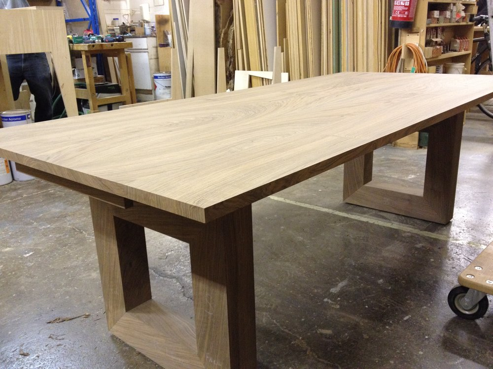Solid walnut dining table with extension leaves, sits eight to twelve  Solid walnut, supported by two cube pedestals. Two leaves attach to the ends of this square table, allowing twelve people to be comfortably seated. Designed to fit with an existing set of Eames dining chairs.