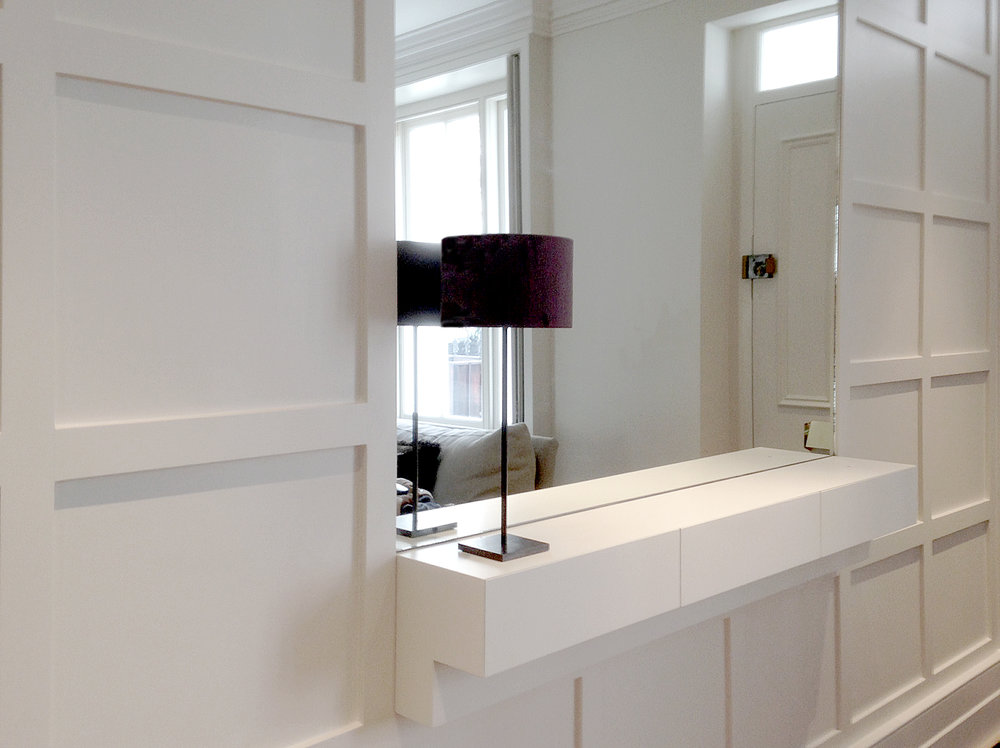 Hallway paneling with built in shelf unit and mirror  Frame and panel design with inset mirror and hallway display shelf, lacquered finish.