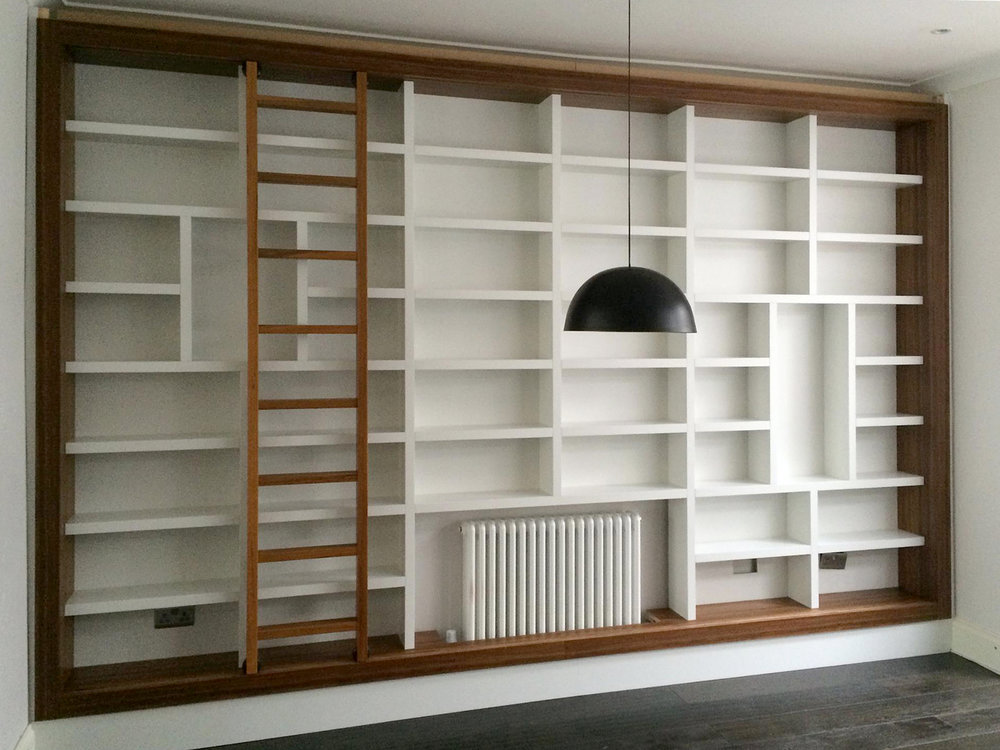 Teak framed built-in library with rolling ladder  Bespoke built-in library and Integrated rolling ladder with concealed wheels. This fixed-shelf cabinetry was carefully designed to hold specific objects and books.