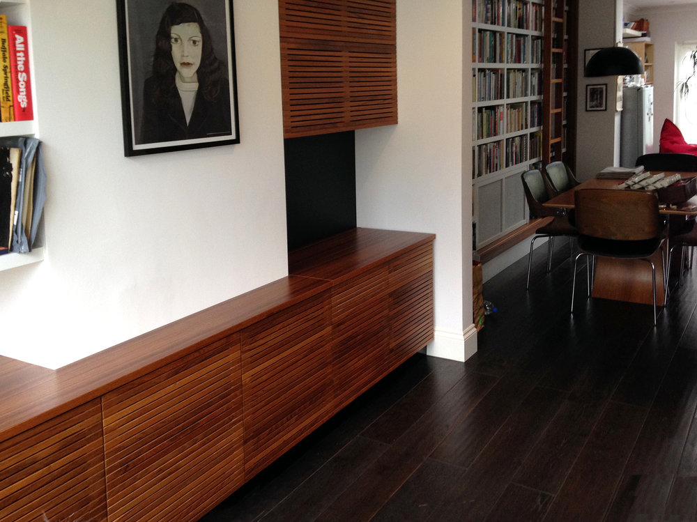 Solid teak turntable and TV cabinetry console and storage  Built-in concealed turntable and TV cabinets with slatted teak fronts and a library with integrated rolling ladder