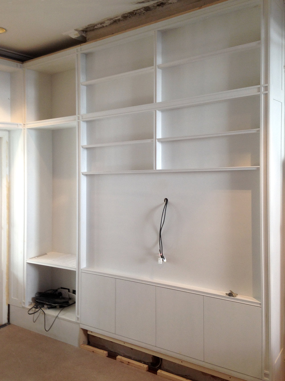 Built-in library with traditional detailing, primed & ready for restored cornice & hand-painted finish  Fixed shelving for varying book heights and TV alcove, commissioned for a private client in London.