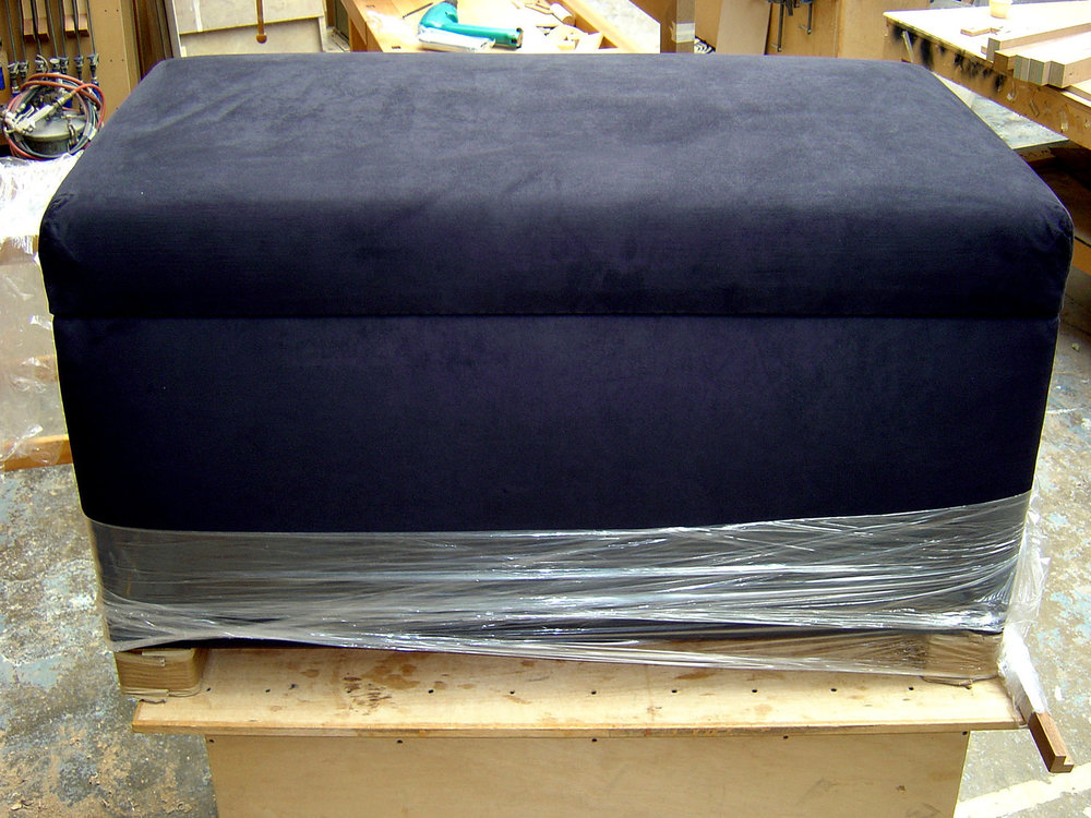 End of bed ottoman chest upholstered in dark blue suede with concealed automated TV lift in lid