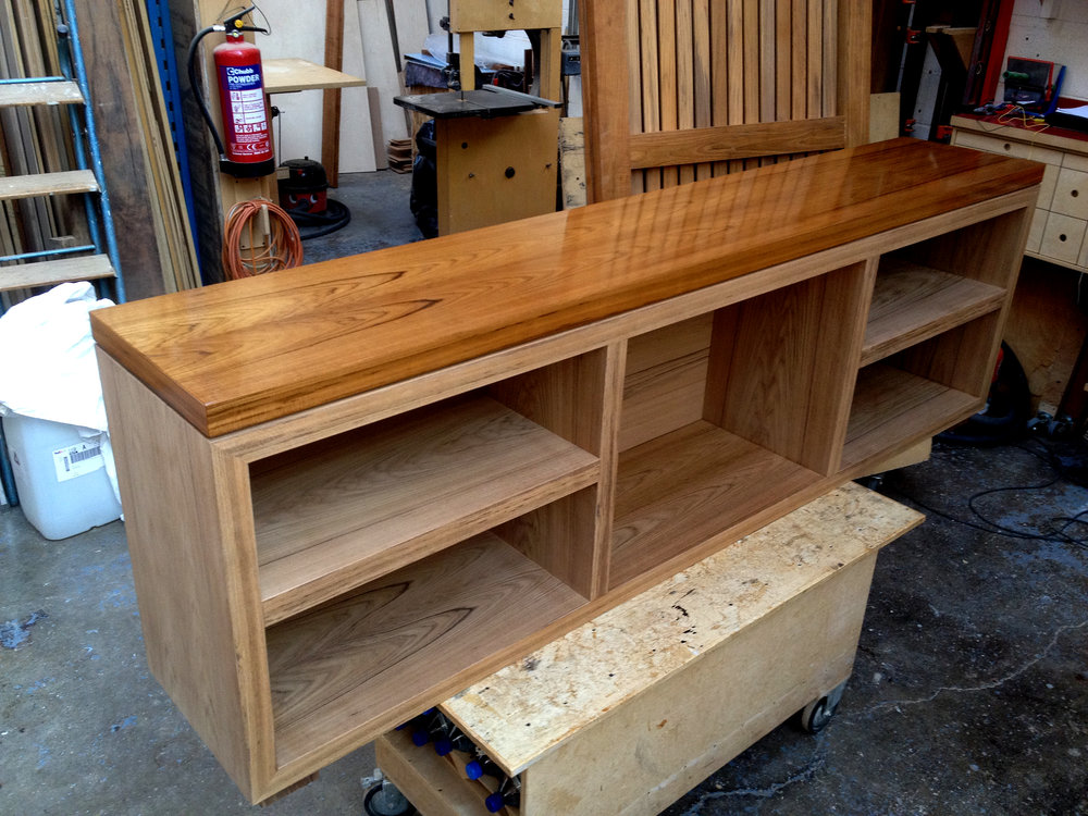 Solid teak sideboard cabinet with marine lacquered gloss top for the deck of a private yacht.