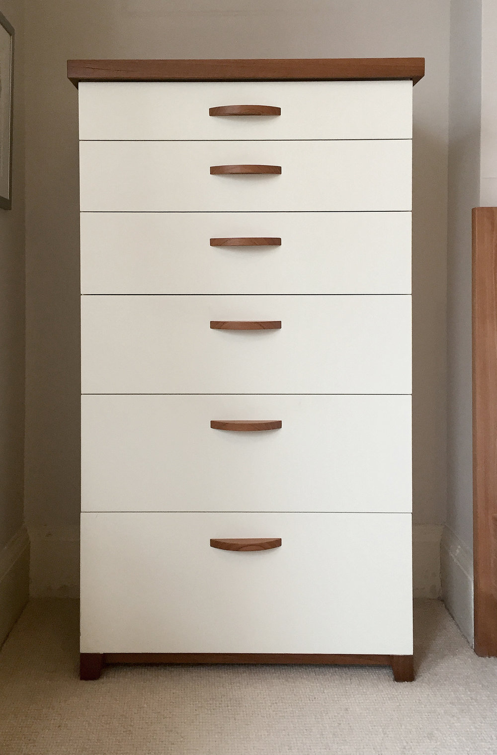 Tallboy dresser with solid teak top, feet and base and handles.