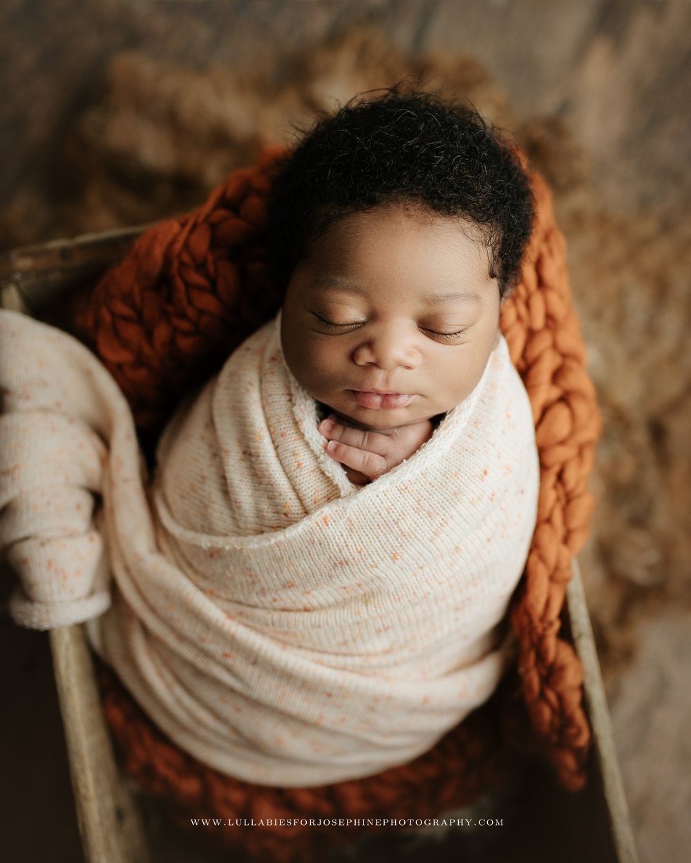African american newborn baby wrapped with cream fabric inside a crate