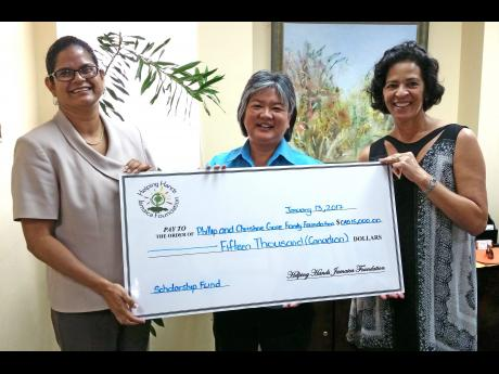 Karen McDonald-Gayle (left) of the Helping Hands charity organisation hands over a cheque to Dr Susan Chang-Lopez (centre), of the Reach Up and Learn Programme and head of the Epidemiology Research Unit at the University of the West Indies (UWI), and Christine Gore, director, Gore Family Foundation.