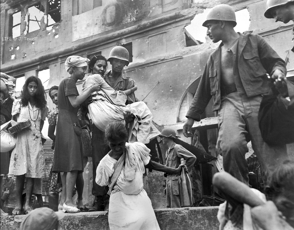 Filipinos being rescued by American soldiers after being held hostage by the Japanese.