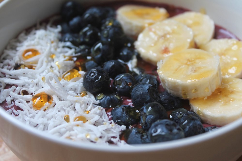 Acai bowl with banana, blueberries, coconut flakes and honey