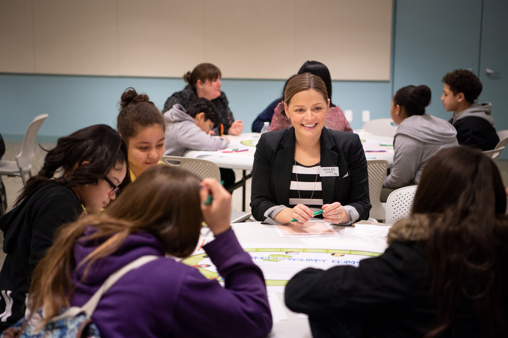 Ashlee Accetta, JA board member and community relations manager at Fidelity Investments, works with Del Sesto Middle School students as part of Congressional Leaders Day during Education Awareness Week.