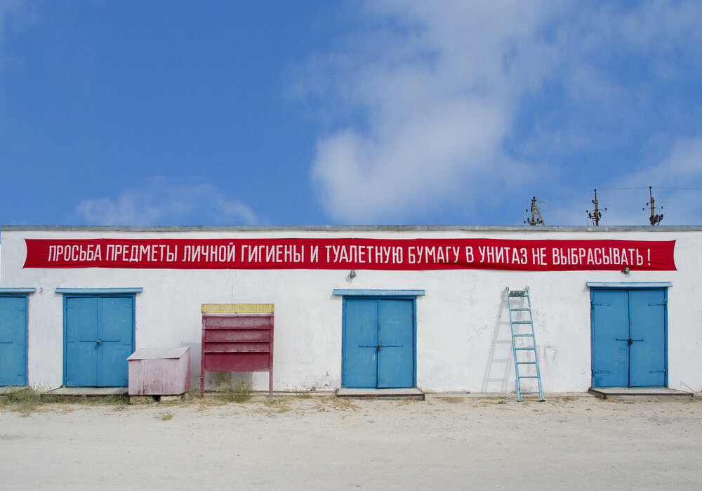 "All types of Soviet propaganda slogans had one thing in common – nobody had read them, but they were everywhere. ""Please do not throw paper to the toilet"" - an attempt to destroy historical memory, as a factor of manipulation of mass consciousness.   Slogan   2015, installation. 1500x75, slogan on fabric."