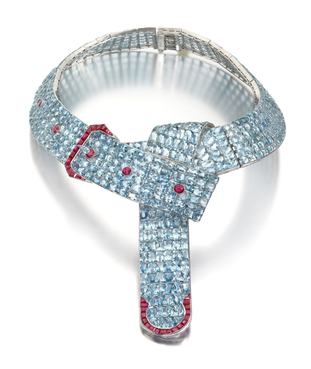 Aquamarine and Ruby Belt with a Buckle Necklace Designed by Fulco, Duke of Verdura, for Paul Flato.New York, circa 1935. Semi-flexible band of pave-set fancy brilliant-cut aquamarines accented with contrasting oval-cut and fancy-cut rubies detailing the buckle, eyelets, and strap trim. Mounted in platinum. 566 aquamarines and 39 rubies.