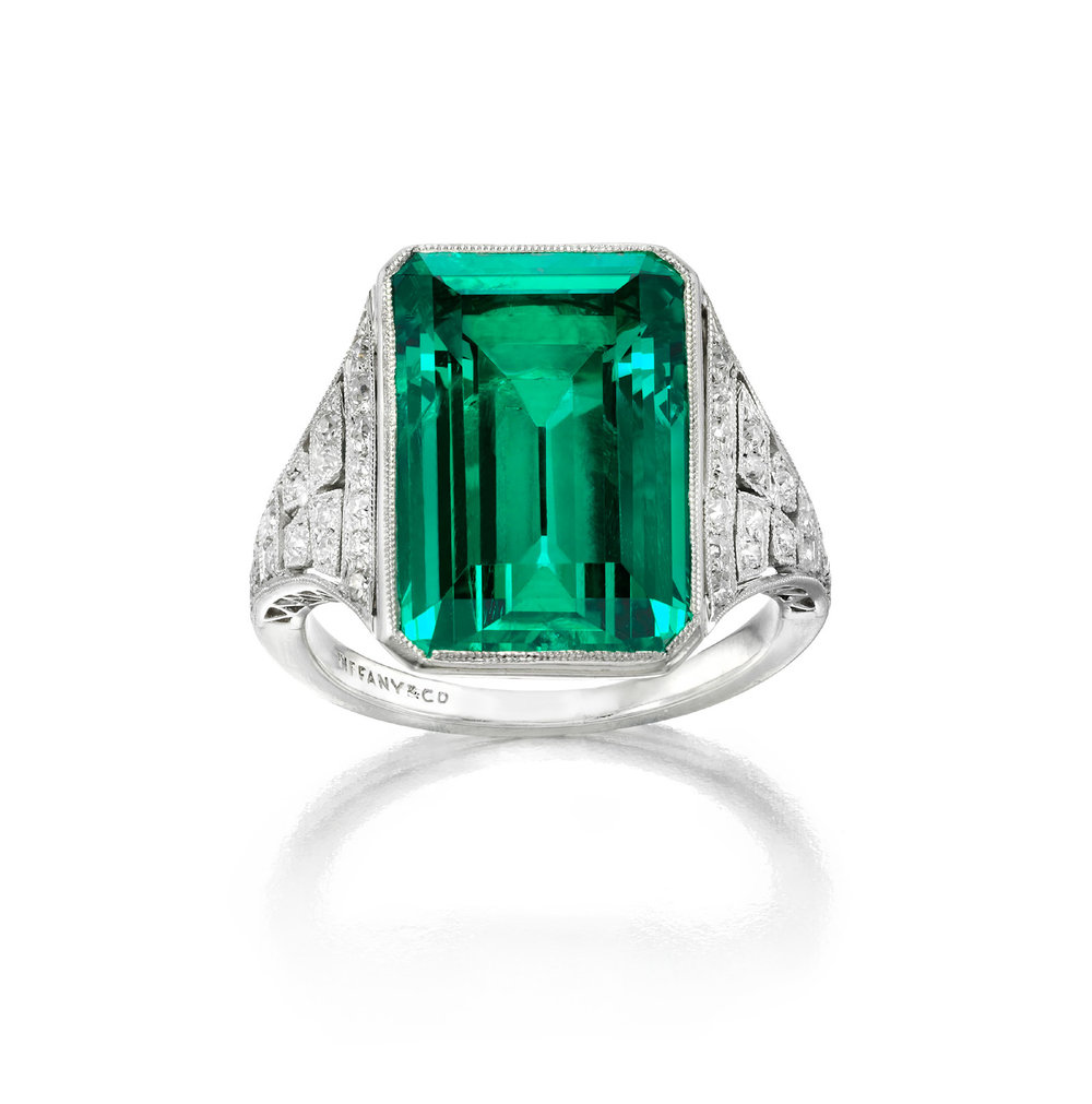Art deco emerald and diamond Ring by Tiffany & Co., New York, circa 1925, for Helen Hay Whitney.Emerald-cut emerald in a millegrain bezel accented on the sides with old European-cut diamonds in millegrain settings, creating a four-leaf form. Mounted in platinum. 1 emerald, 8.51 carats; 34 diamonds, .50 carat.