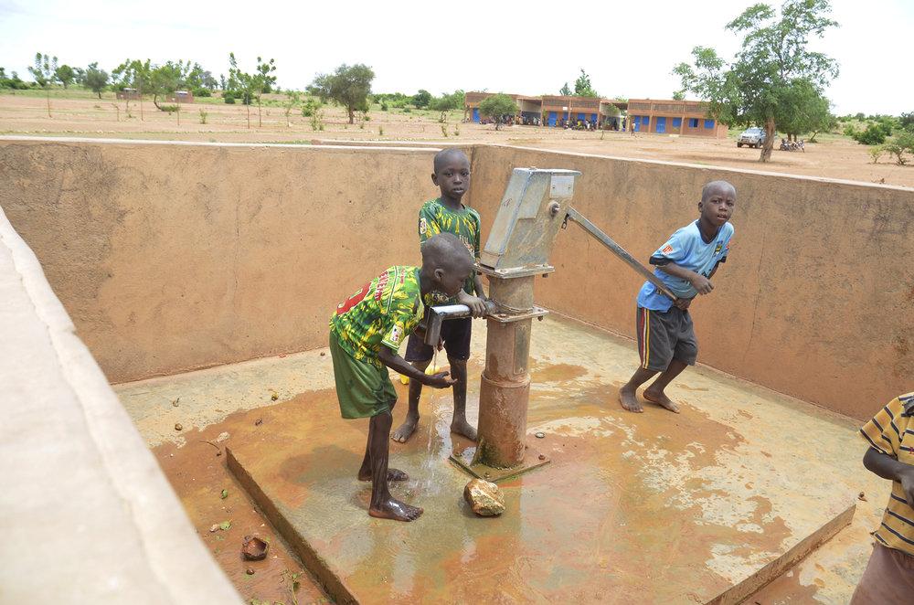 Skolebarn henter vann i brønnen