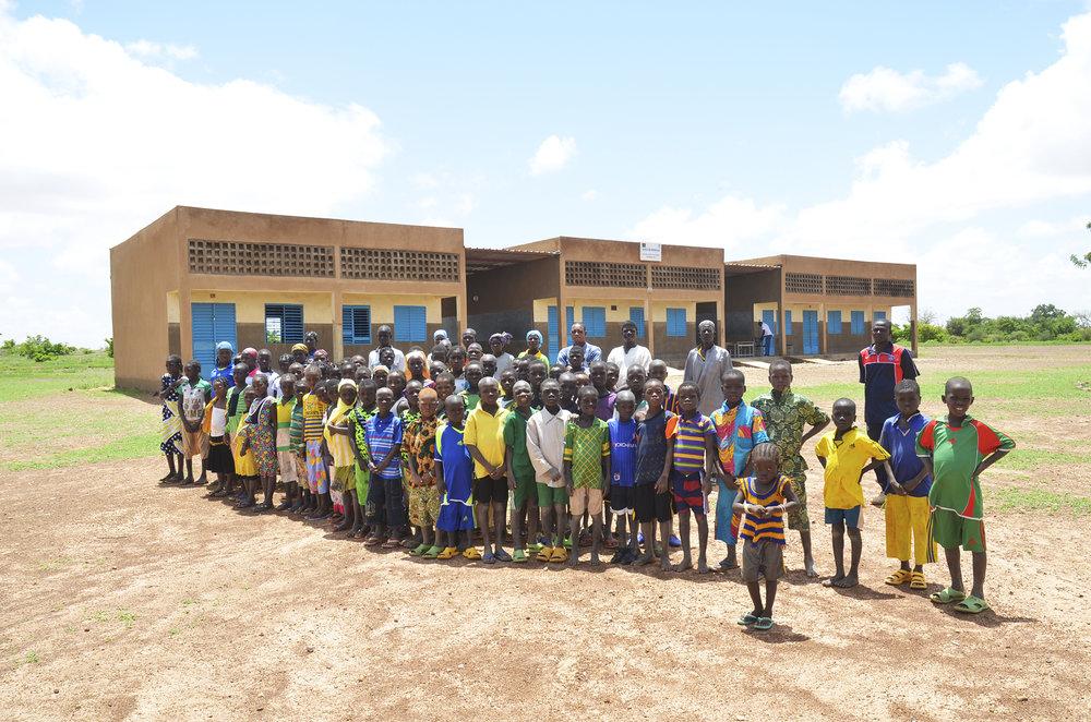 Elever og lærer foran skolen