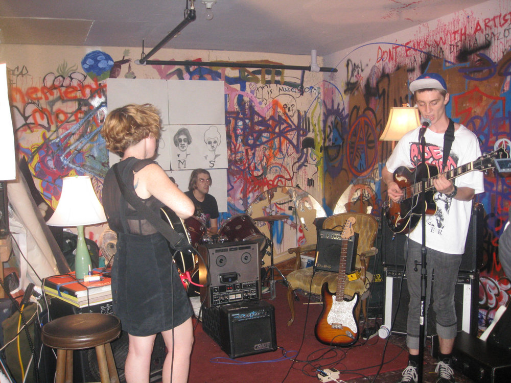 "EXAMINER.COM Interview: Moms   Playing a first show on a bus at the Albany Landfill isn't much of a conventional beginning for most bands, but Moms, an Oakland-based band that is part rock, part surf and part noise, is not necessarily the conventional type anyway.  For starters, consider the band members themselves: a rough amalgamation of misfit kids spanning a five-year age gap who rehearse in a warehouse and play noisy, riffed-out, lo-fi rock'n' roll.  There's  Chris Alarie  (vocals, guitar, drums), the soft-spoken unofficial front man who is far more protopunk than he probably realizes. Occasionally trading places with Alarie is the baby of the group, newly-19-year-old  Dallin Kapp  (drums, guitar, vocals), who is as unassuming as he is spirited.  Alexis Faulkner  (saxophone, bass, vocals) serves as the foursome's even-keeled center, with her frank and meaningful insight. And just as every band needs its diva, Moms has  Amy Silbergeld  (vocals, bass). Known in musical circles as Amy Aimless, Silbergeld fills the shoes of the assertive and oft dramatic frontwoman who is in it just as much for the image as she is for the music.  How the band came together is a story not unlike many other bands. Alarie and Faulkner met while attending high school in Santa Rosa, Calif., where both were active in the local music scene. Similarly, Kapp (a native of Indian reservation-turned-town Roosevelt, Utah) and Silbergeld (from Seattle, Wash.) met at  California College of the Arts , where both are currently students.  The two worlds collided when Silbergeld went to a show at  Mama Buzz  and happened upon Alarie performing solo. ""I thought, 'He's the next big…whatever,'"" she said.  The two exchanged numbers in hopes of playing together, and after a short stint as a joke band,  The Eegles , they got a bit more serious about writing and playing music, first adding Kapp to the lineup (""I just learned how to play drums with this band,"" he admitted) and eventually Faulkner. After a mere two months of existence, the band has two shows and nearly a dozen songs under its belt, and there are no signs of slowing down. While Moms only counts a bus and a warehouse on its list of show locations, the band has plans to play house shows and legitimate venues alike.  ""We're going to try and play as many shows in as many different places as we can,"" Alarie said from his perch on the edge of a couch in the Moms practice space. ""Hopefully…we will be equally as comfortable playing in somebody's garage and living room or on a bus as we would be playing at more of a…traditional venue.""  Yet it is the shows that fall outside of the spectrum of ""normal"" that the band believes will be most advantageous for its growth, as Oakland arguably has a larger underground than mainstream scene.   ""The character of the city lends itself to more non-traditional venues,"" Alarie said, speaking of the spread-out nature of Oakland. ""There are a lot more warehouses…and weird, old, abandoned buildings.""  Silbergeld also attributed the versatility of the scene and the strong sense of community to people's openness to mixed-media collaborations.  ""People want to combine art, shows, music,"" she said. ""There [are] a lot of good opportunities to meet other people who are doing similar stuff or want to put together weird shows that aren't just a band playing in a room.""  But it also helps that Silbergeld is the ""social networker"" of the group, whose duties extend beyond singing and playing and into finding and promoting shows.  ""I know everyone and everyone loves me,"" a half-clad Silbergeld explained between cigarette drags.  The band already has two future shows lined up and eventual plans to record. While the details are still under discussion, the first recording will most likely be released as a limited edition cassette.  And while each of the members have side projects (some with other people, some with one another) in varying states of array and disarray, all four members can agree that they don't want Moms to be a short-lived, one-off kind of band, rather one that evolves and grows.  ""We hope to be as famous as Michael Jackson,"" Faulkner said with a smile."