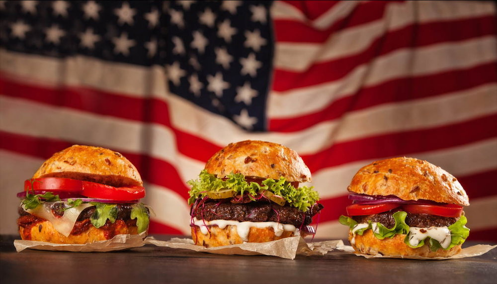 Three burgers in front of an American flag. © Shutterstock