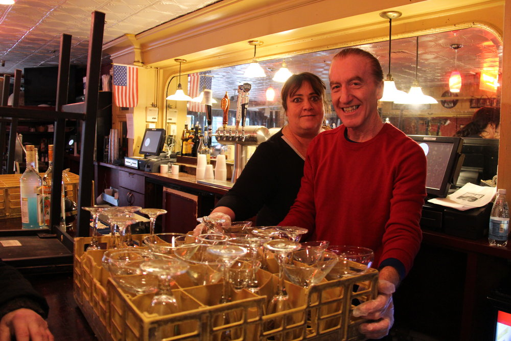 Laura Seluta, 30 year veteran waitress, helps Frank Cirigliano, shift leader, stack glasses, box up bottles of liquor, and clear off the long wooden bar in Durgin-Park's Gas Light Pub. Photo: Karen Bento