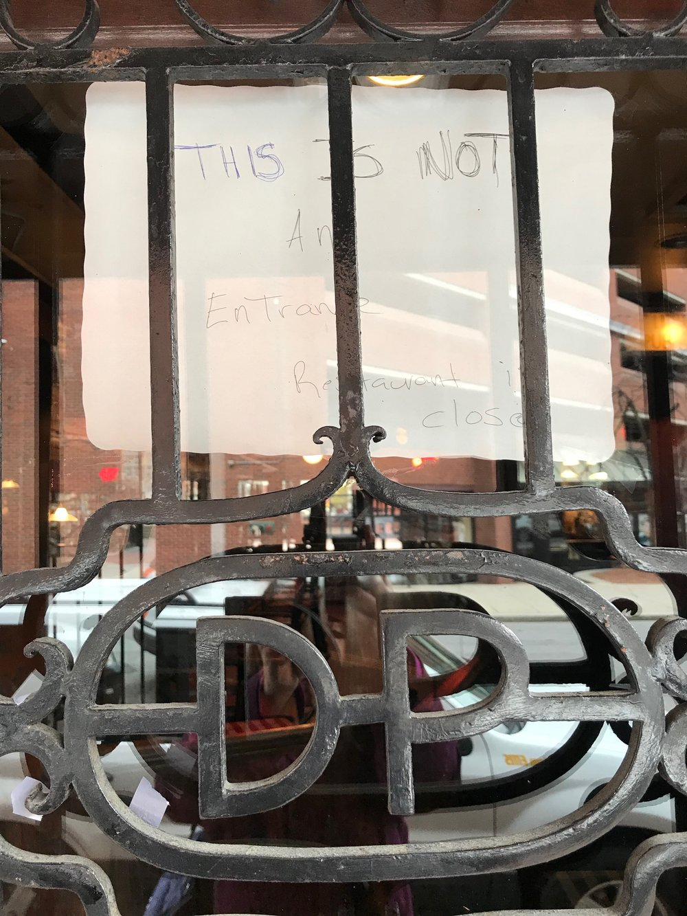A handwritten note scrawled on the back of a paper placemat and taped to the the Clinton Street entrance door, behind the restaurant's black, wrought iron D-P door grate. Photo: Karen Bento