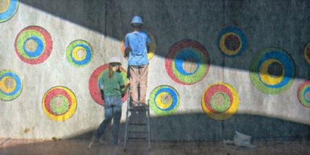 Zarah Daniels left and Nate Murano work on a mosaic installation at the new Kansas Humane Society building near K-96 and Hillside.    Wichita artist Tina Murano created the artwork.