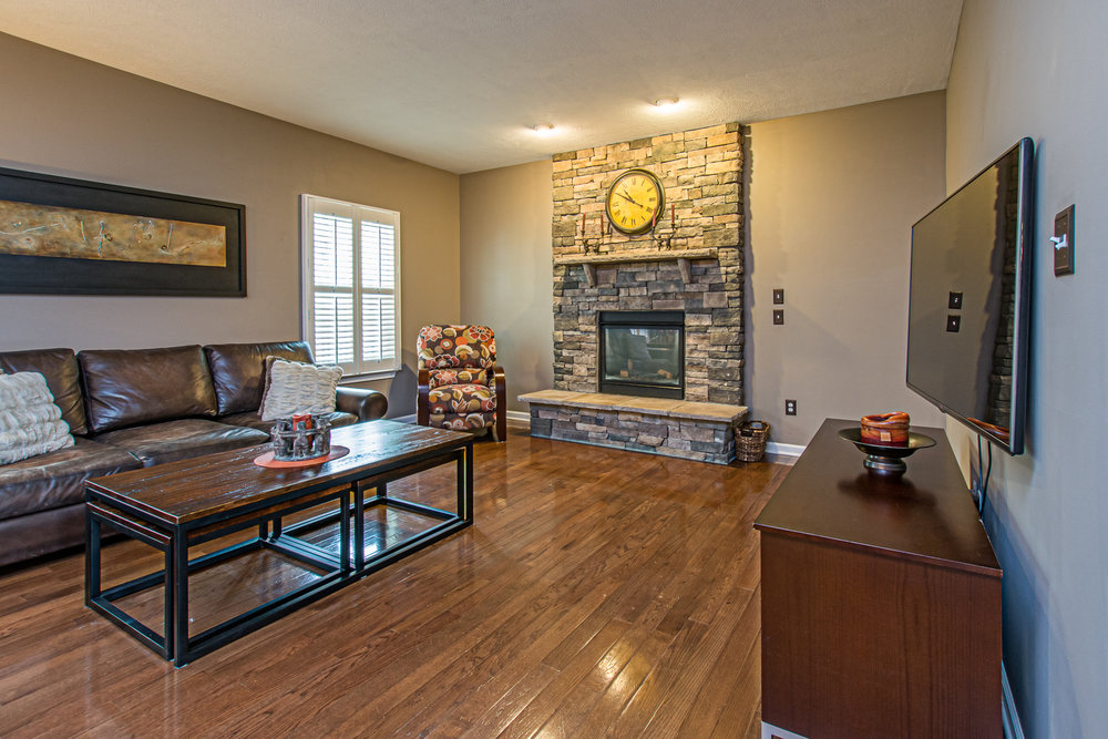 Living area with hardwood floors and stone fireplace