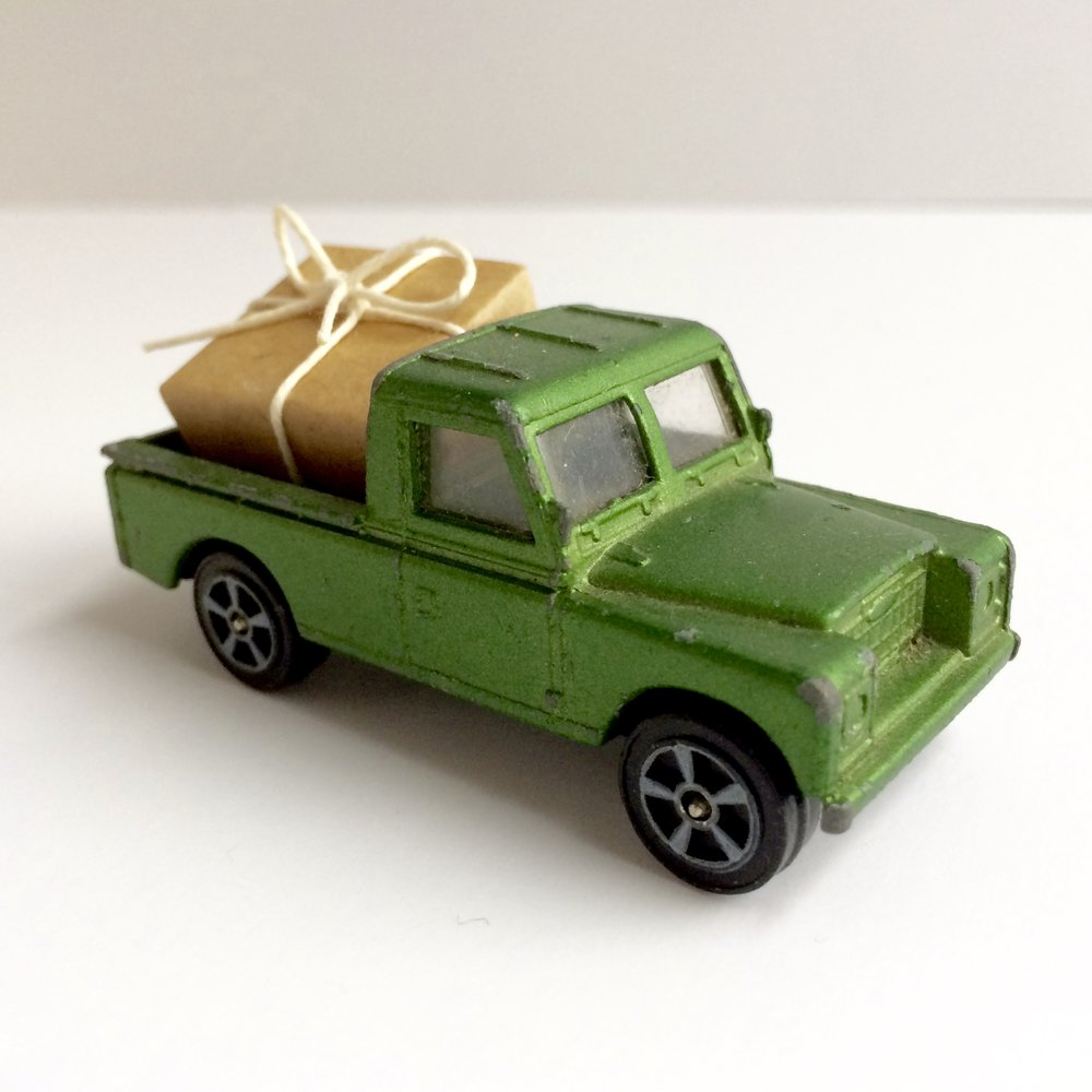 Miniture toy truck moving a gift