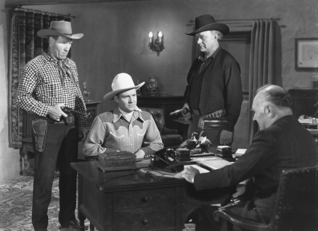 "Frank McCarroll and Tex Terry force Gene Autry to confer with Charles Evans in ""Twilight on the Rio Grande."""