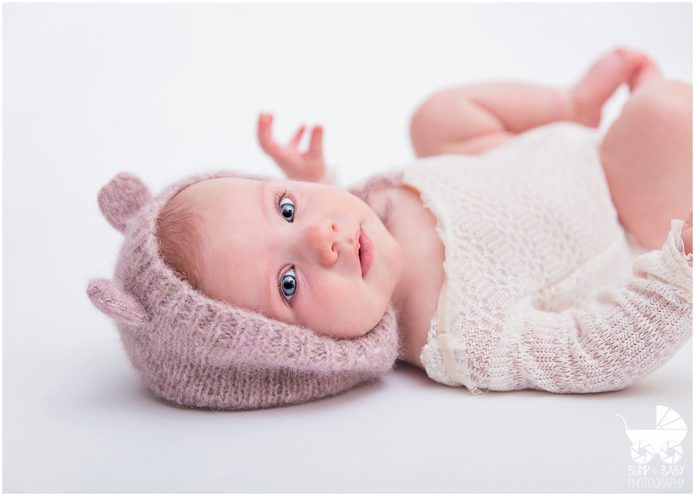 3-Month-Old-Baby-Girl-Looking-at-Camera-with-Teddy-Bear-Hat.jpg