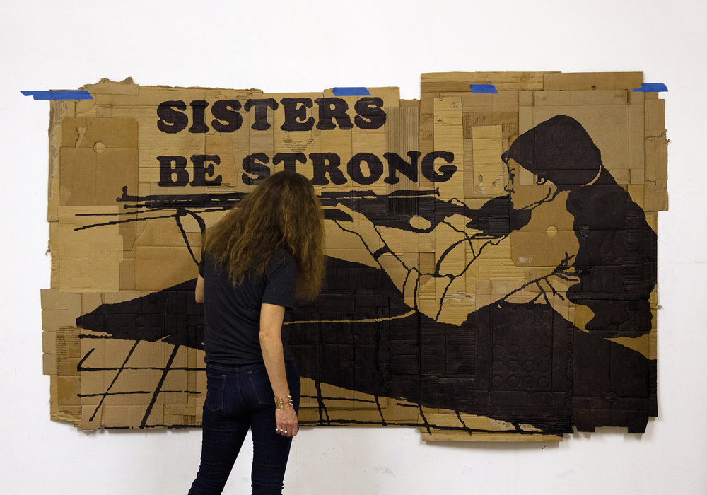 The feminist Andrea Bowers finishing a cardboard painting, 2013