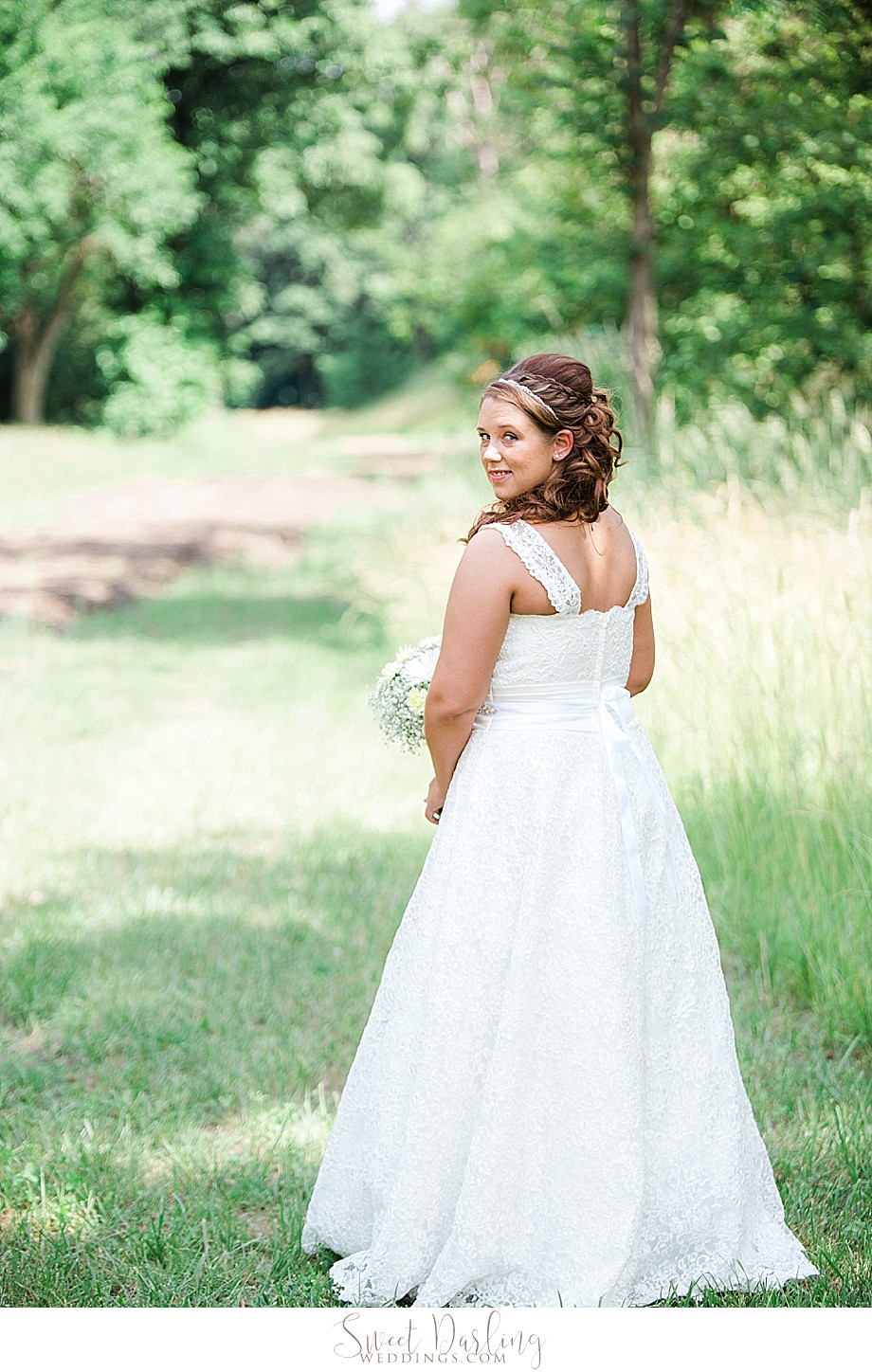 Bride in white lace wedding dress outdoors