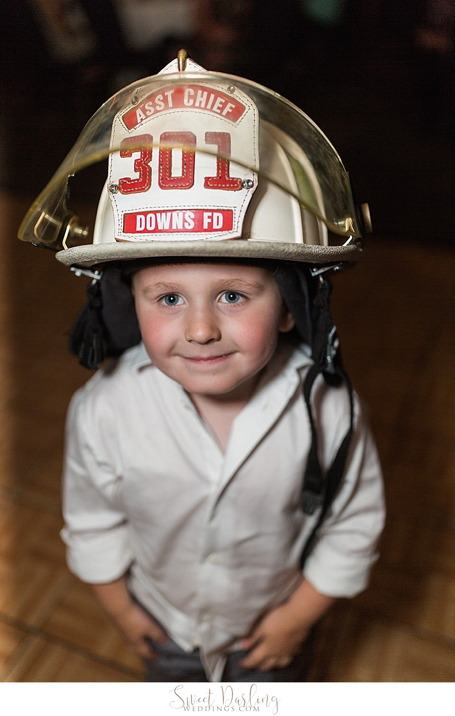 Ring bearer wearing EMS fire chief hat of deceased father of groom