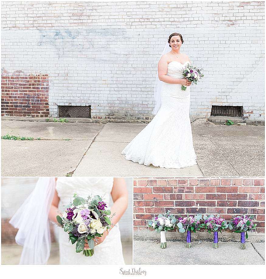 bride holds wedding bouquet by brick wall
