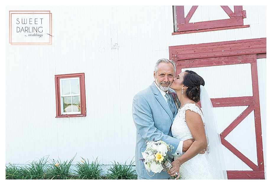 bride kissing dad outside barn