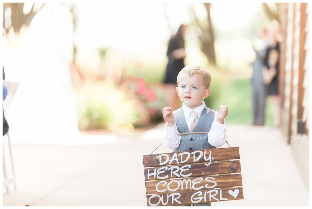 Ring bearer with sign at outdoor wedding ceremony