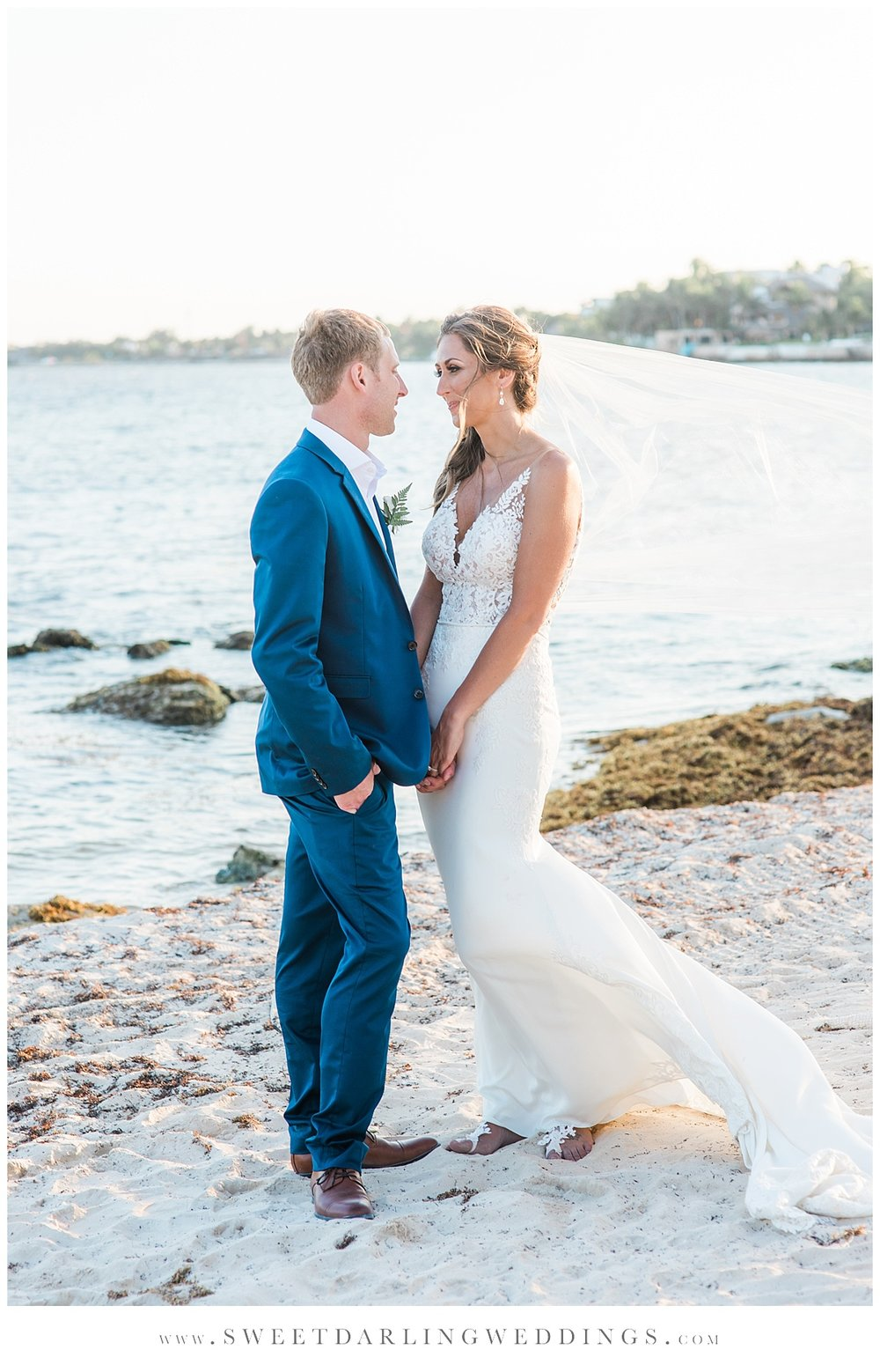 Bride and groom in dark blue suit on beach before destination wedding at Secrets Silversands